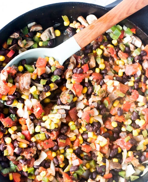 Black beans, corn, peppers, onions, cilantro in a cast iron skillet with a spoon.