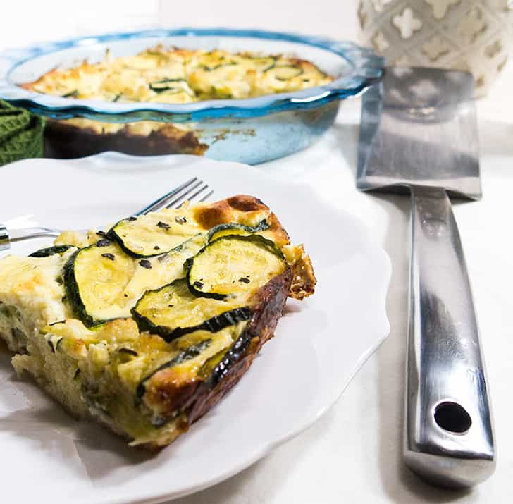 Zucchini pie on a white plate with a silver fork. Pie in background and a silver spatula for serving.
