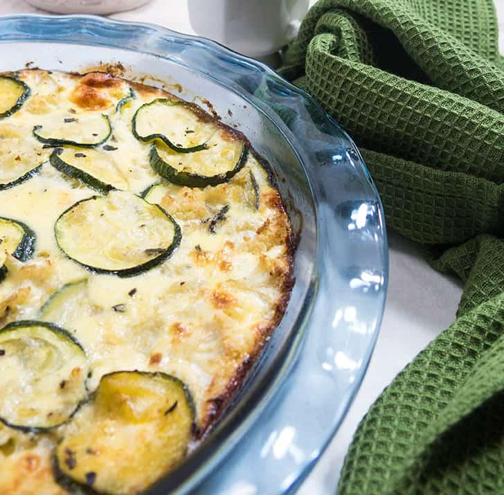 Zucchini Cauliflower Pie in clear blue pie plate with green napkin beside it
