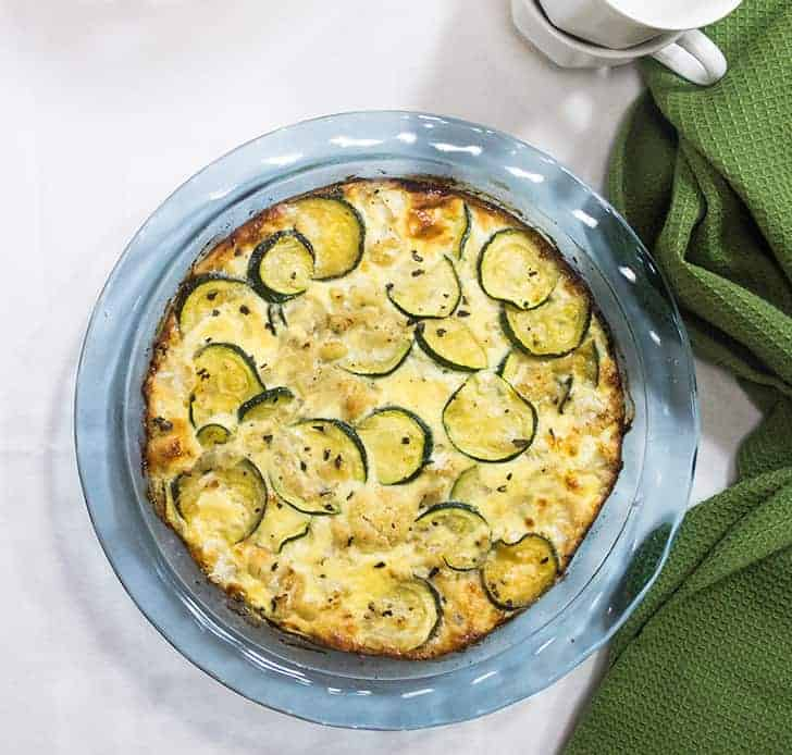 Zucchini Pie in a clear blue glass pie plate with a green napkin beside it