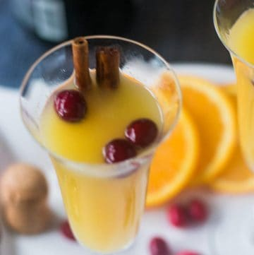 Mimosa in a champagne glass with cranberries & cinnamon sticks