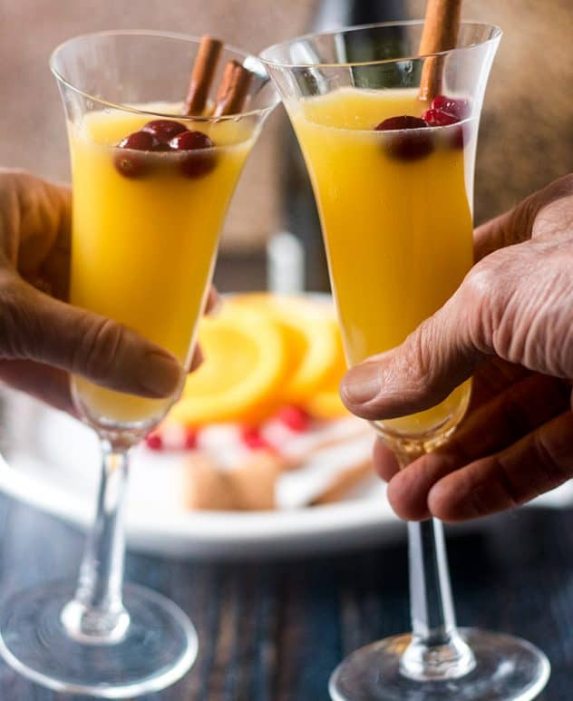 Mimosa in champagne glasses with cinnamon sticks & cranberries