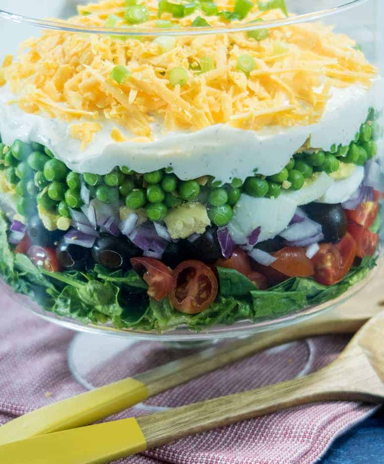 Simple Make Ahead 7 Layer Salad in clear glass bowl with two wooden salad spoons for serving.