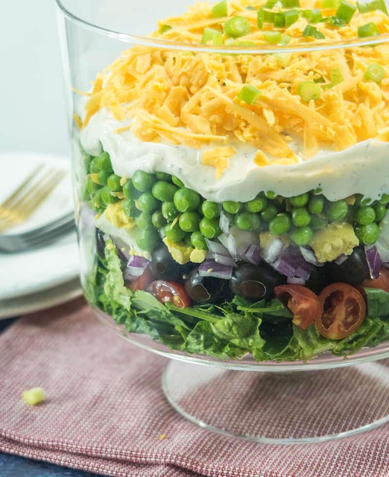 Simple Make Ahead 7 Layer Salad in a clear glass serving bowl. two plates in the background with forks for serving.