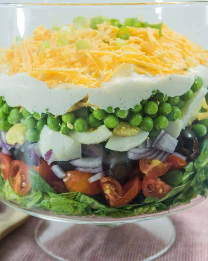Simple Make Ahead 7 Layer Pea Salad in a clear glass serving bowl