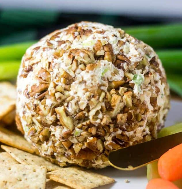 Cheese Ball on a plate with crackers, celery, & carrots.