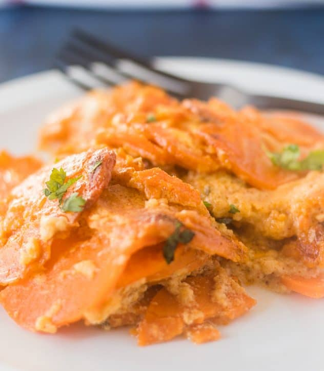 Spicy Scalloped Sweet Potatoes on a white plate with a black fork.