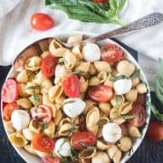Caprese Pasta Salad in a bowl with a spoon and tomatoes and basil beside bowl.