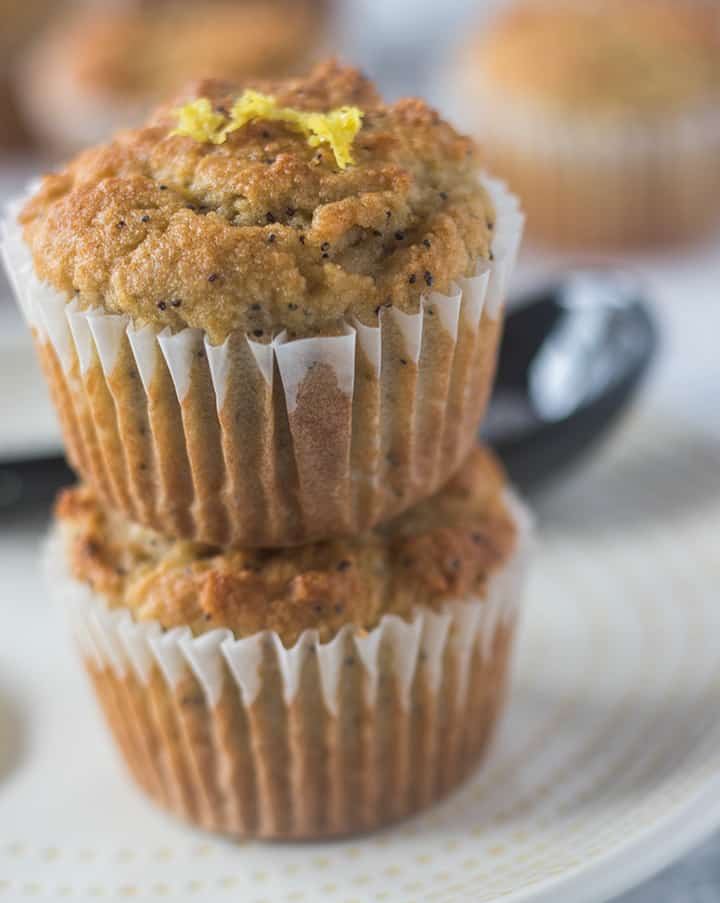 Lemon Poppy Seed Muffins stacked on top of each other and garnished with fresh lemon zest.