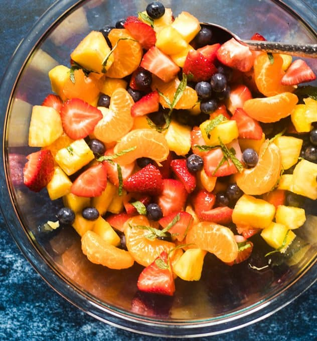 Fruit salad in a large glass serving bowl.