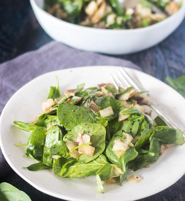 Caramelized Cabbage and Warm Spinach Salad on a white plate with a fork and grey napkin