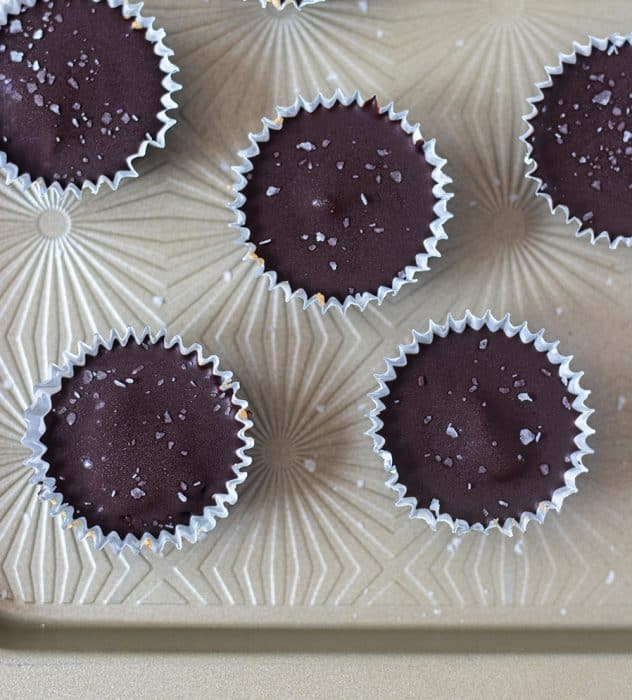 Dark chocolate cashew butter cups in muffin liners on baking pan.