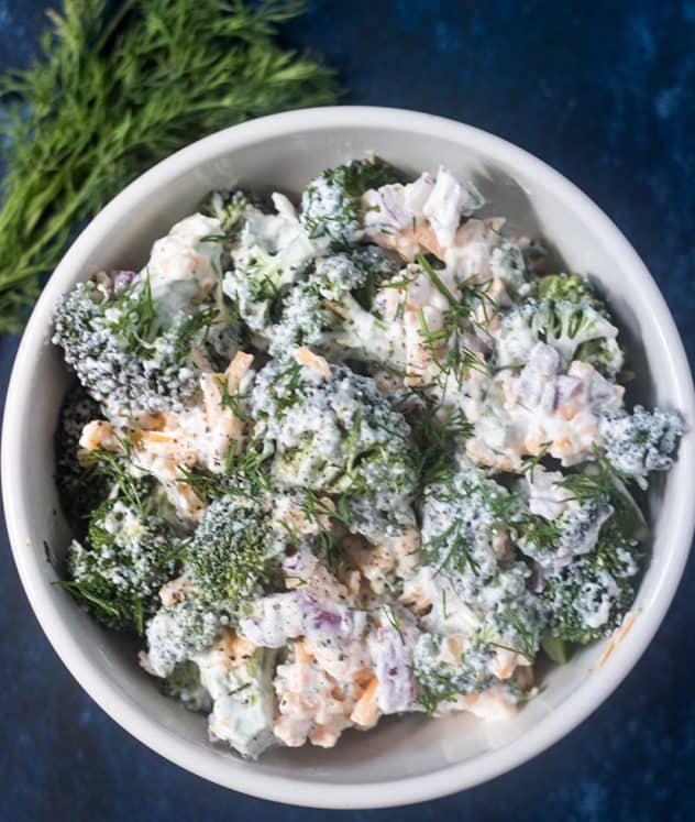 Broccoli Salad in a white bowl with fresh dill weed beside it.