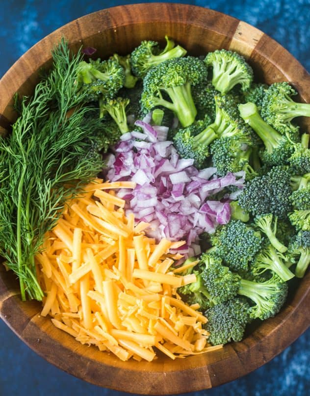 broccoli florets, red onion, cheddar cheese and dill weed in a salad bowl.