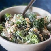 Broccoli Salad in a white bowl with a silver serving spoon.