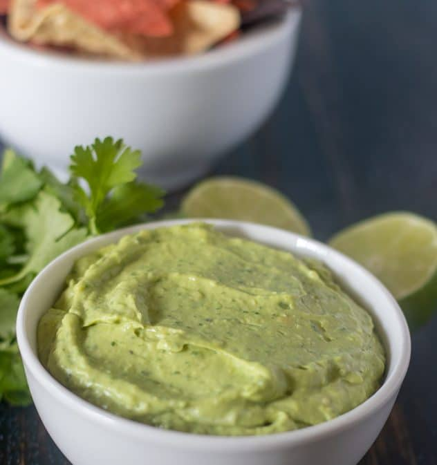 Avocado dip in a white bowl with chips in background.