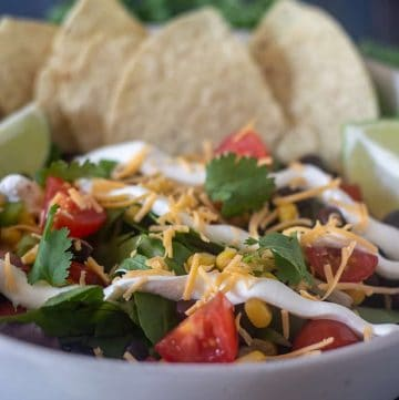 Black Bean Taco Salad in a bowl with tortilla chips and toppings
