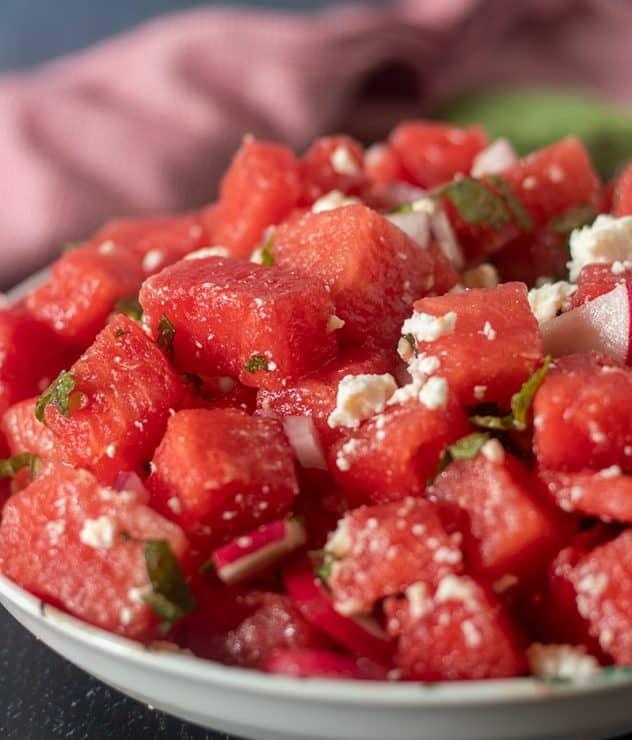 Watermelon Feta Mint Salad is a white serving bowl.