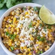 Mexican Street Corn Salad in a bowl topped with feta cheese and a lime wedge.