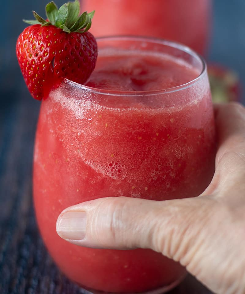 Watermelon Strawberry Wine Slushies in a glass and holding one with hand.