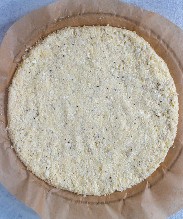 Cauliflower Pizza Crust on lined circular plate.