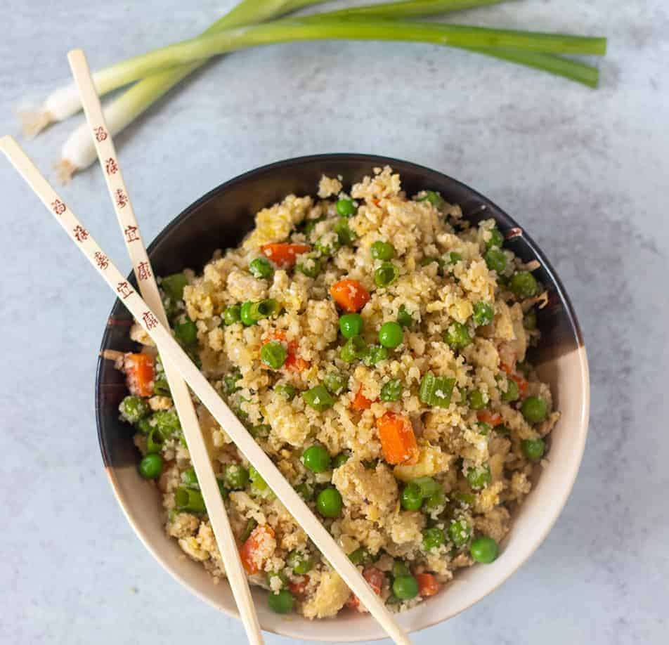 Cauliflower Fried Rice in a bowl with some chopsticks and scallions in the background.