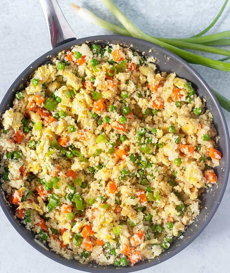 Cauliflower Fried Rice in a skillet with scallions in the background.