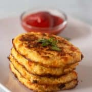 Cauliflower Hash Browns stacked on a plate with some ketchup in a bowl.