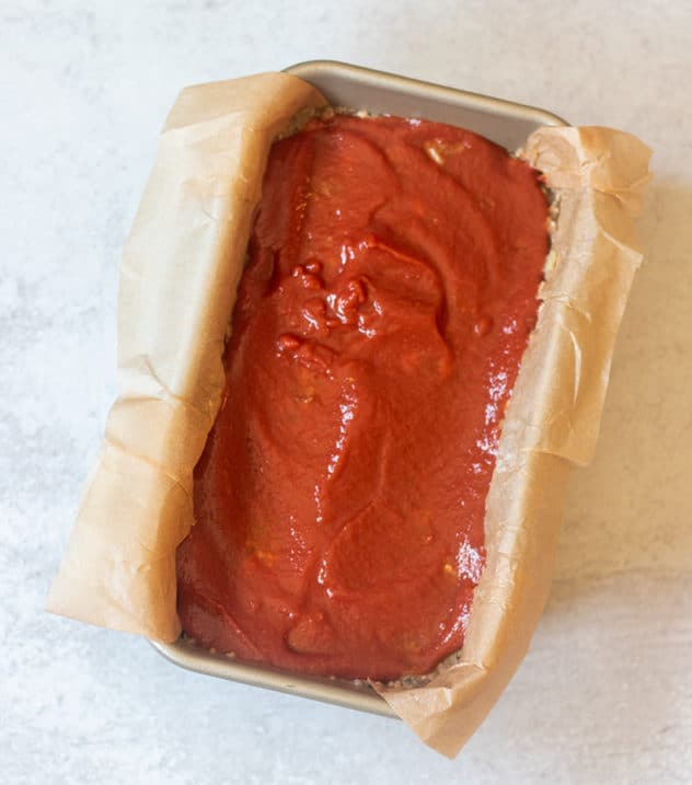 Lentil loaf topped with sauce prior to baking.