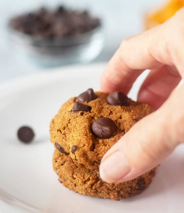 Pumpkin Chocolate Chip Cookies on a plate and grabbing one with a hand.