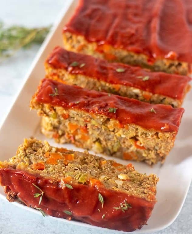 Lentil Loaf on a white serving plate garnished with fresh thyme.
