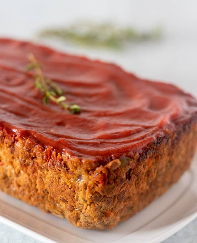 Lentil loaf on white serving plate garnished with fresh thyme before slicing.