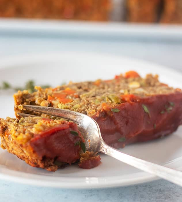 Slice of lentil loaf on a white plate with a silver fork.