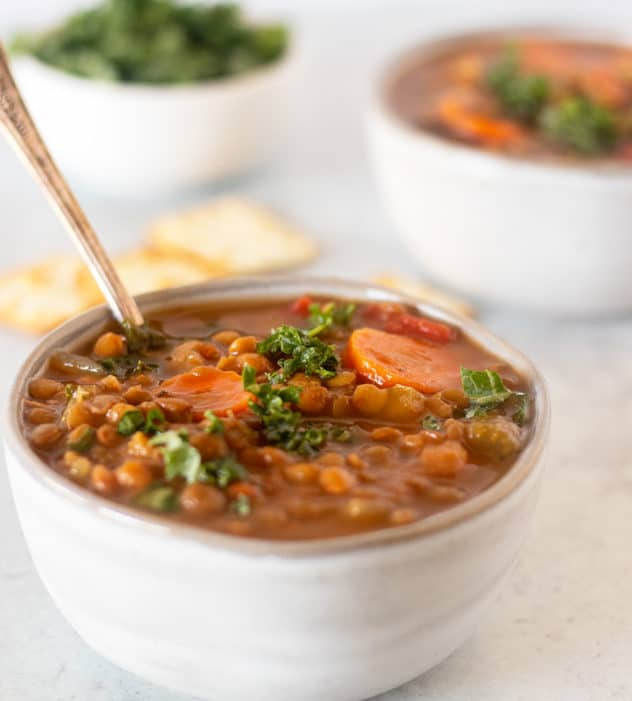 Slow cooker lentil soup in a bowl with a spoon topped with fresh chopped kale and crackers beside it.