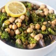 Broccoli Chickpea Salad in a white bowl garnished wit a lemon slice