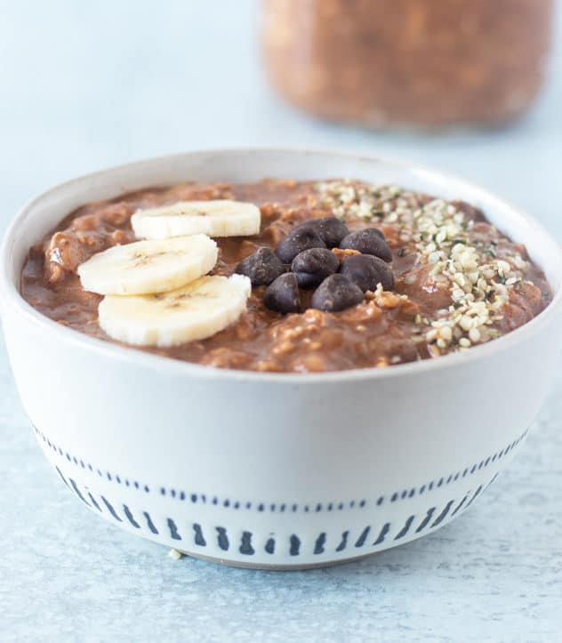 Chocolate Overnight Oats topped with bananas, dark chocolate chips and hemp seeds.