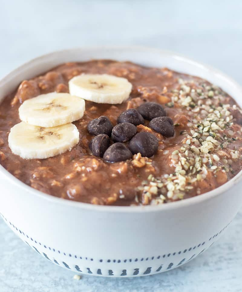 chocolate overnight oats topped with banana slices, dark chocolate chips and hemp seeds.