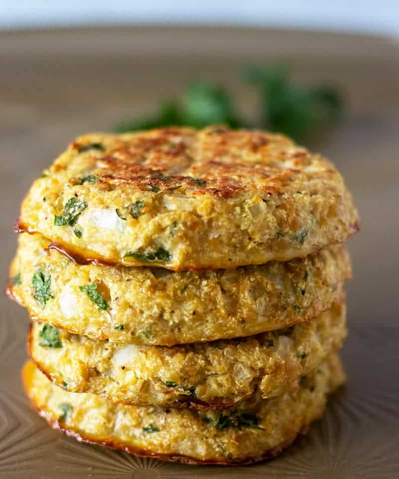 Chickpea burgers baked on a pan stacked.
