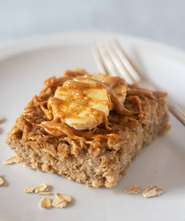peanut butter banana baked oatmeal on a plate topped with bananas and peanut butter