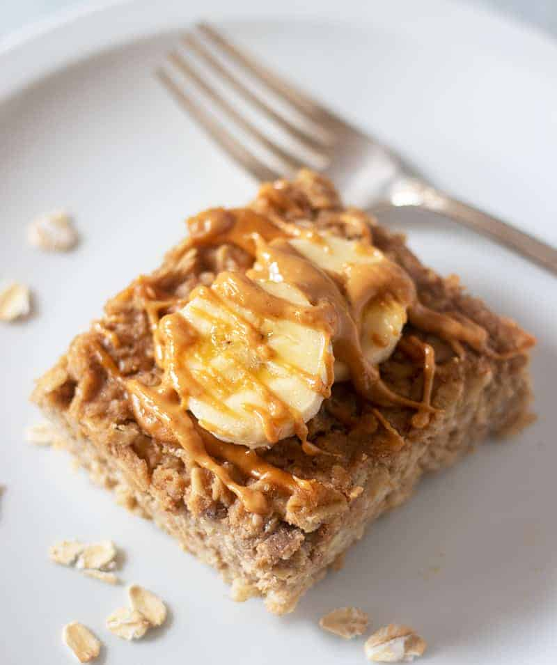 Peanut Butter Banana baked oatmeal on a plate topped with banana slices and peanut butter.
