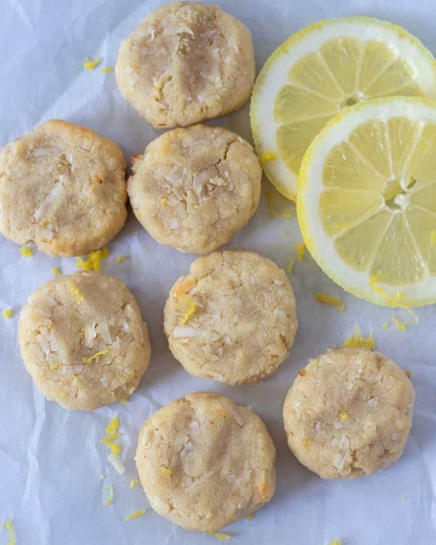 lemon cookies on parchment paper with lemon slices and zest