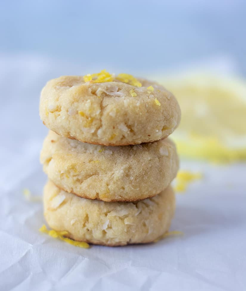 lemon cookies stacked with lemon slices in background