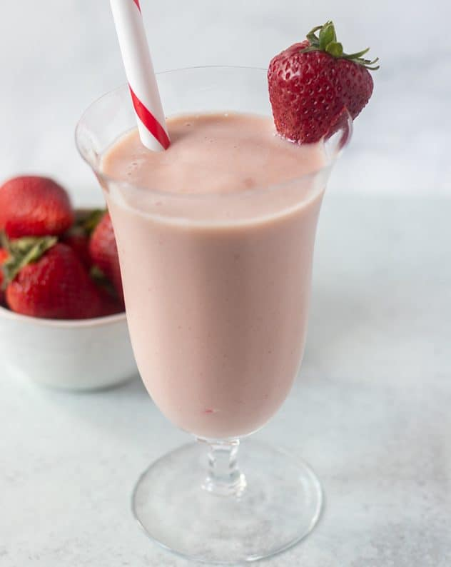 Strawberry milkshake in a glass with straw and garnished with a fresh strawberry. Bowl of strawberries in the background.