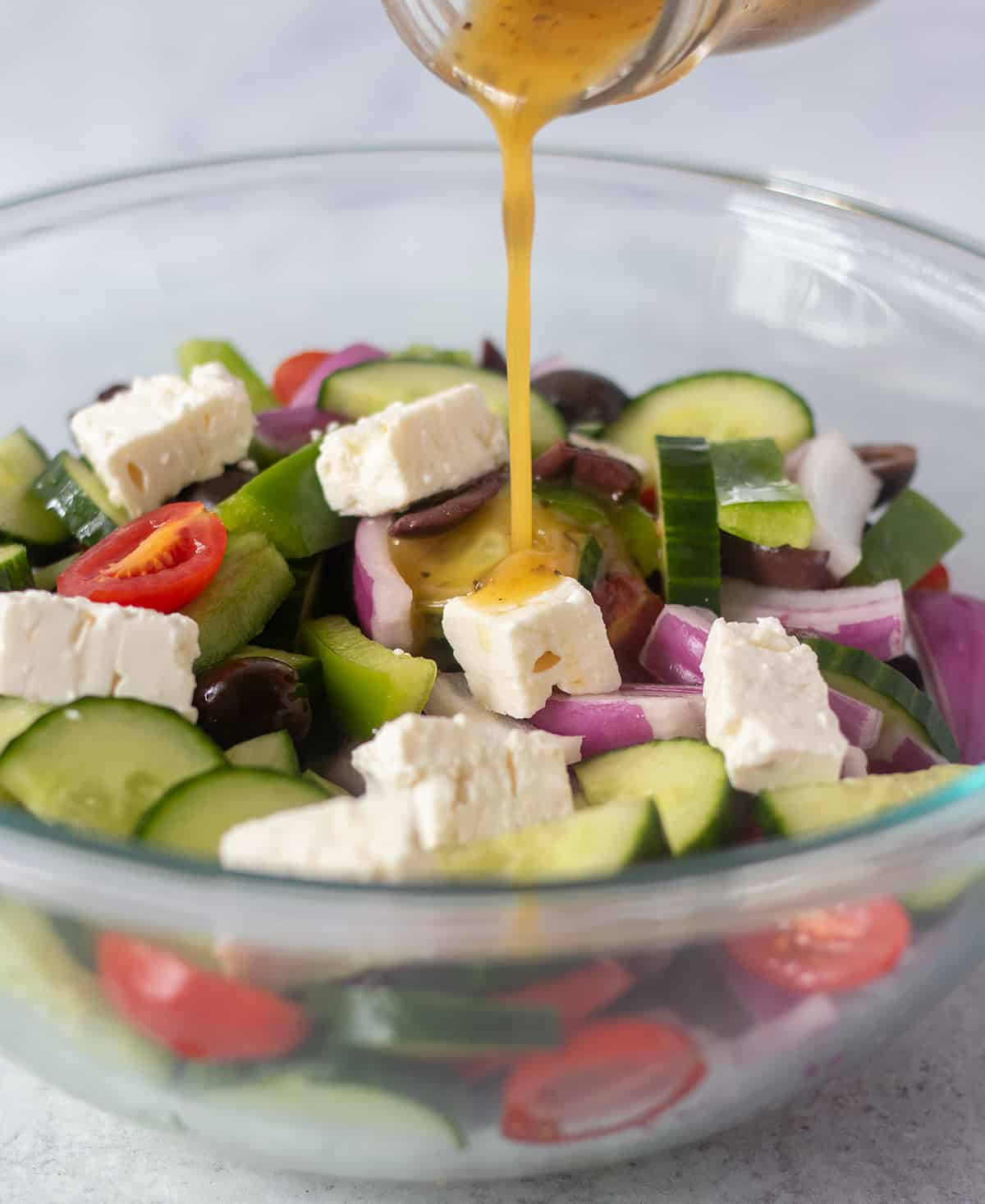 Salad dressing being drizzled on to greek salad