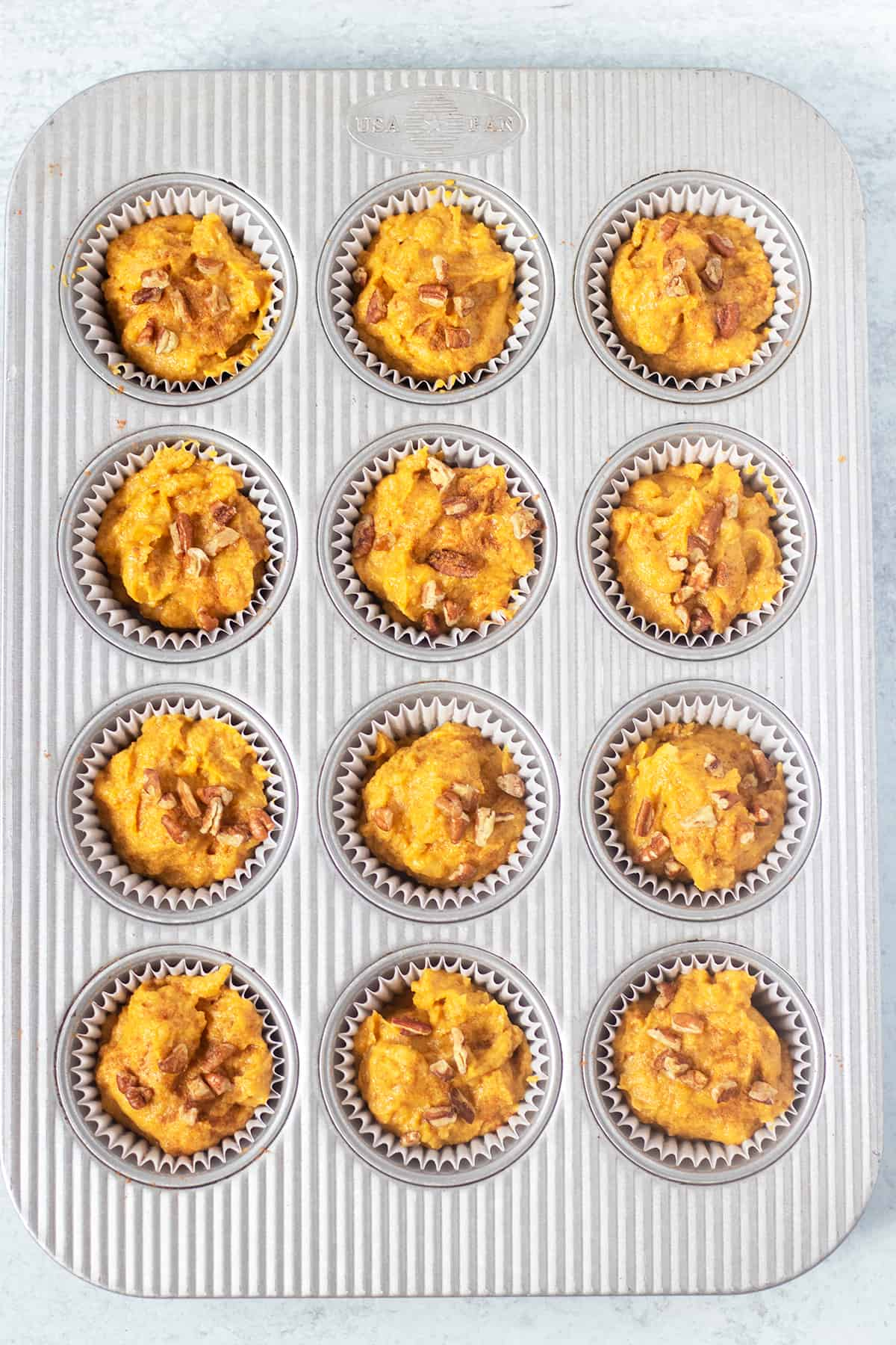 pumpkin muffins in pan lined with baking cups prior to being baked