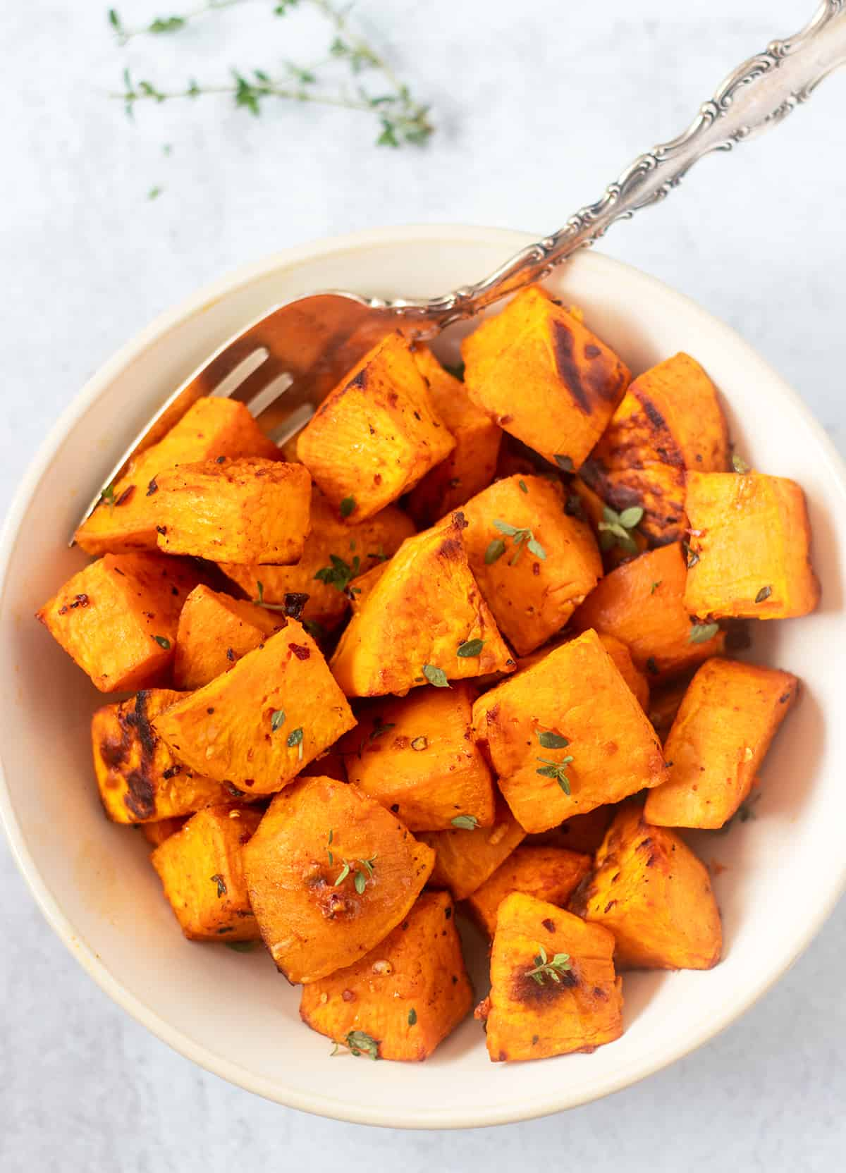 sweet potatoes in a serving bowl topped with fresh thyme