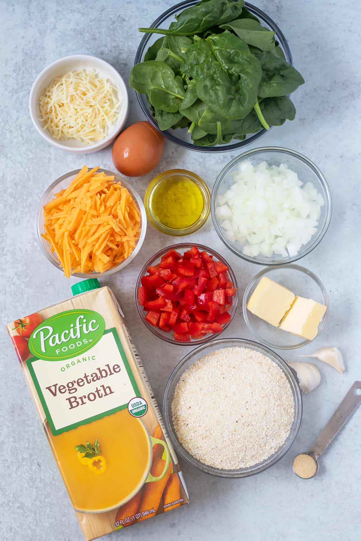 spinach, chopped onion, chopped bell pepper, parmesan cheese, cheddar cheese, egg, olive oil, butter, garlic, grits, vegetable broth