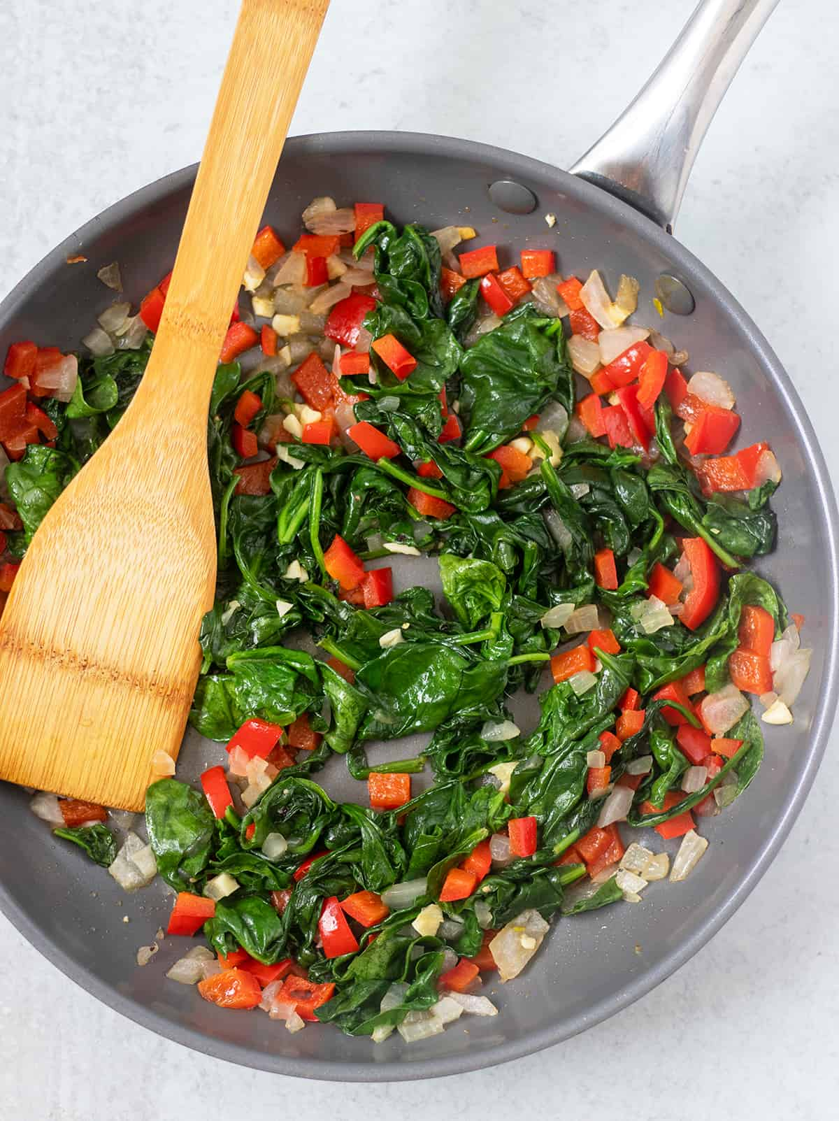 spinach, onion, garlic, and bell pepper being cooked in pan with wooden spoon
