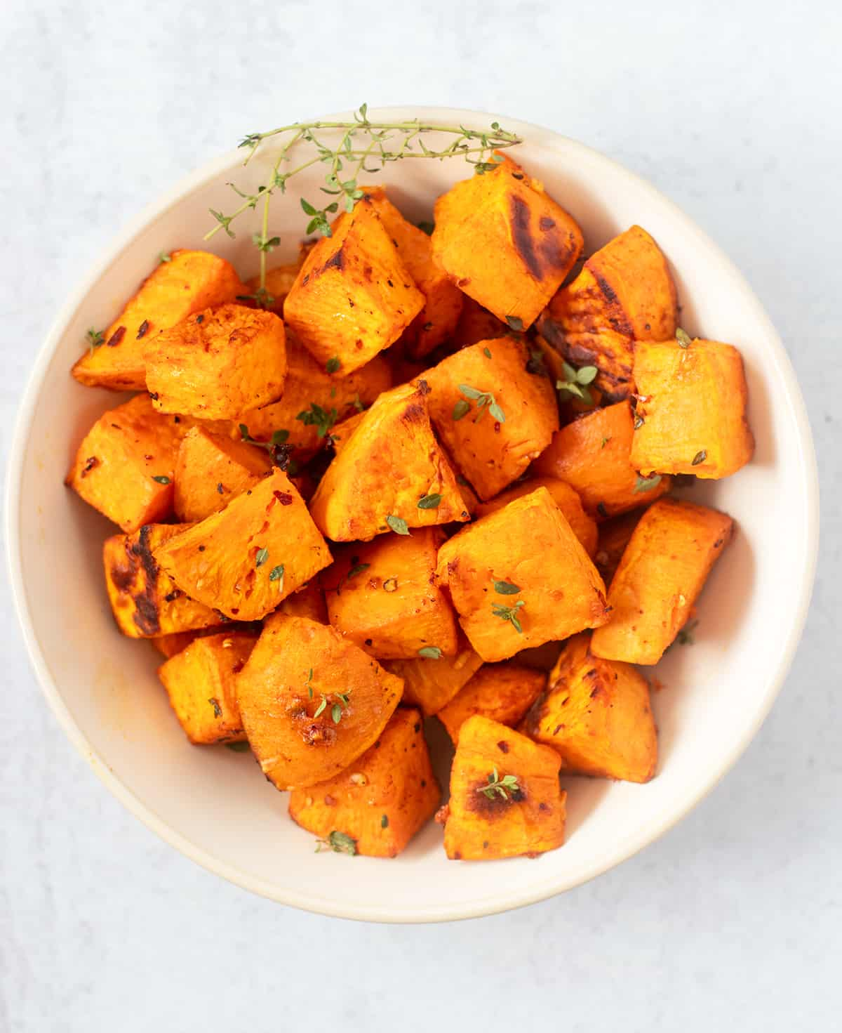 roasted sweet potato cubes in a white serving bowl with fresh thyme