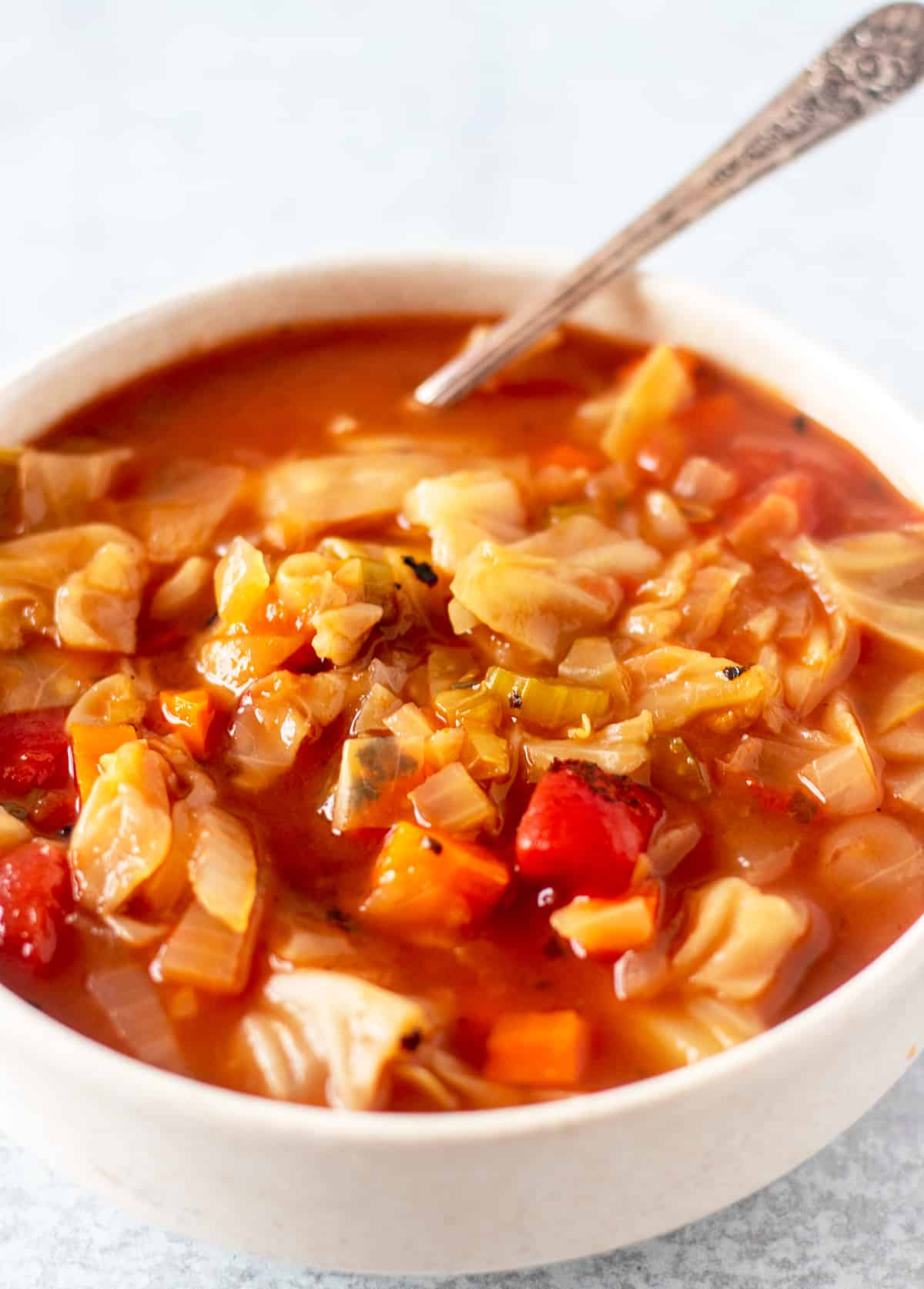 cabbage soup in a white serving bowl with a silver spoon